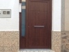Puerta de calle PVC Nogal panel IP7 y fijo lateral y superior